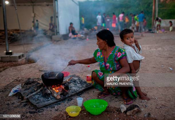 TOPSHOT Members of the Warao tribe Venezuela's secondlargest indigenous group prepare food at the Janokoida shelter where they have been taking...