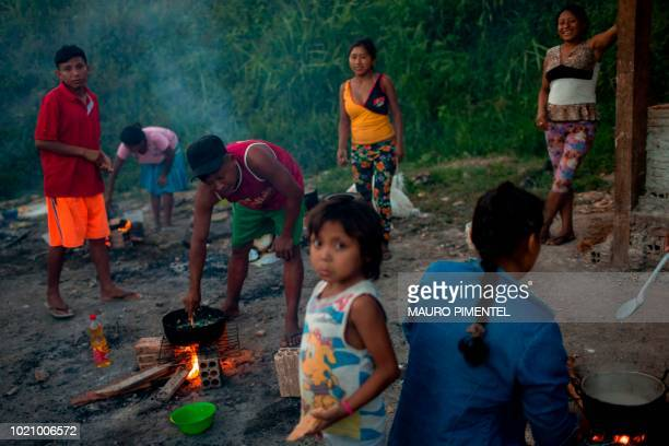 Members of the Warao tribe Venezuela's secondlargest indigenous group prepare food at the Janokoida shelter where they have been taking refuge in the...
