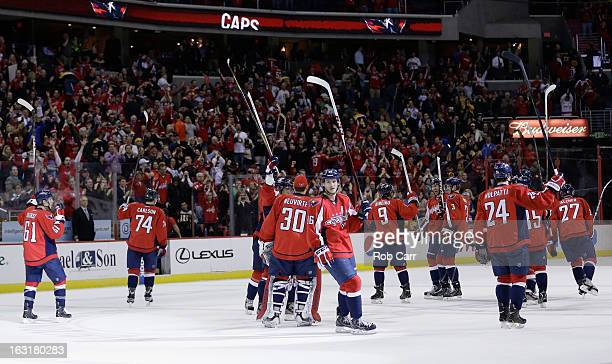Members of the Washington Capitals celebrate on the ice after defeating the Boston Bruins 43 in overtime at Verizon Center on March 5 2013 in...