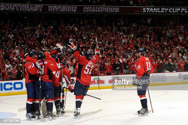 Members of the Washington Capitals mob Braden Holtby after defeating the Winnipeg Jets 53 to win the Southeast Division title at Verizon Center on...