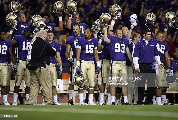 Members of the Washington Huskies football team stand on the sideline raising their helmets during the game against the LSU Tigers on September 5...