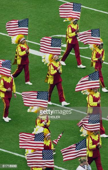 Members of the Washington Redskins honor guard carry US flags during