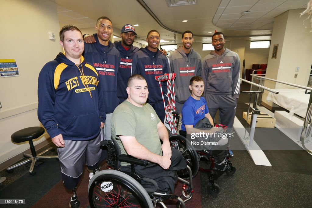Members of the Washington Wizards pose for a soldier with wounded warriors during a visit to Walter Reed Medical Center on October 25, 2013 in Washington, DC.