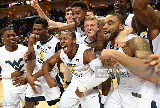 Members of the West Virginia Mountaineers including Jonathan Holton Jevon Carter and Jaysean Paige celebrate after defeating the San Diego State...