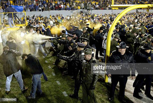 Members of the West Virginia State Police and Campus Police protect their flank against the smaller of the two advancing crowds at Mountaineer...