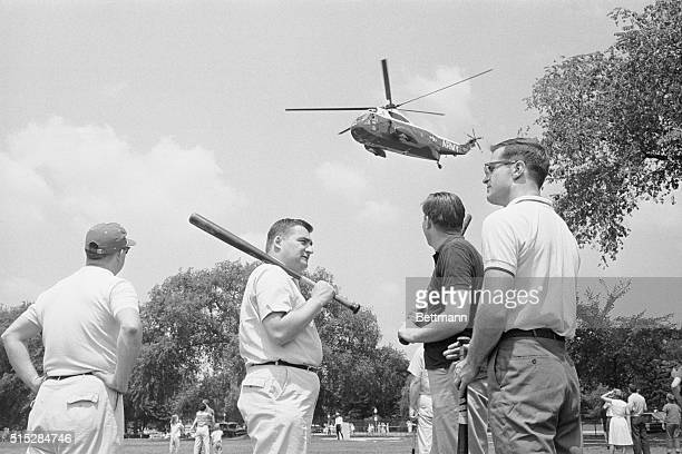 Members of the White House staff pause during a baseball game against members of the Senate Foreign Relations staff while Marine One flies overhead....