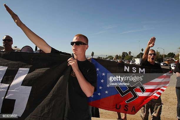 Members of the white supremacist group the National Socialist Movement hold swastika flags and salute at the NSMÕs antiillegal immigration rally near...