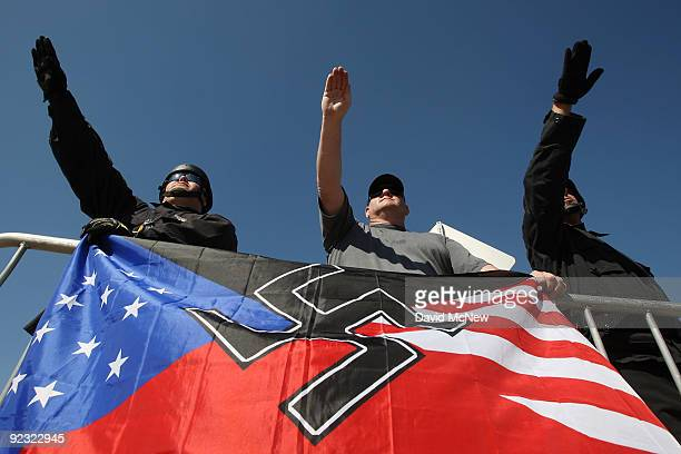 Members of the white supremacist group the National Socialist Movement salute during the NSMOs antiillegal immigration rally near a Home Depot store...