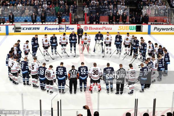 Members of the Winnipeg Jets and Chicago Blackhawks join together at centre ice to observe a moment of silence for the Humboldt Broncos at the Bell...