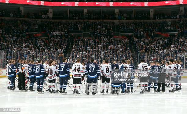Members of the Winnipeg Jets and Chicago Blackhawks stand together around centre ice in solidarity for the Humboldt Broncos prior to puck at the Bell...