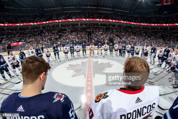 Members of the Winnipeg Jets and Chicago Blackhawks stand together around centre ice in solidarity for the Humboldt Broncos prior to puck drop at the...