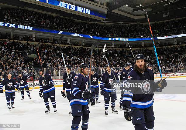 Members of the Winnipeg Jets salute the fans following a 52 victory over the Arizona Coyotes at the MTS Centre on January 26 2016 in Winnipeg...
