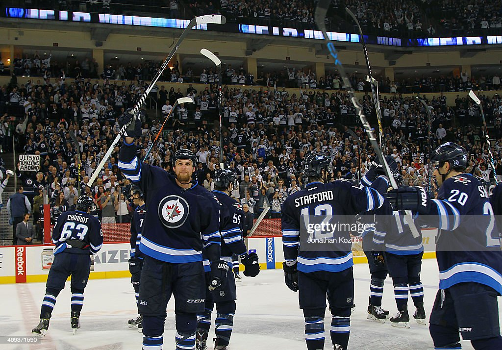 Members of the Winnipeg Jets salute the fans from centre ice after closing out the regular season with a 5-1 victory over the Calgary Flames on April 11, 2015 at the MTS Centre in Winnipeg, Manitoba, Canada.