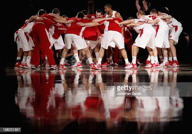 Members of the Wisconsin Badgers huddle together after player introductions before a game against the Ohio State Buckeyes at Kohl Center on February...