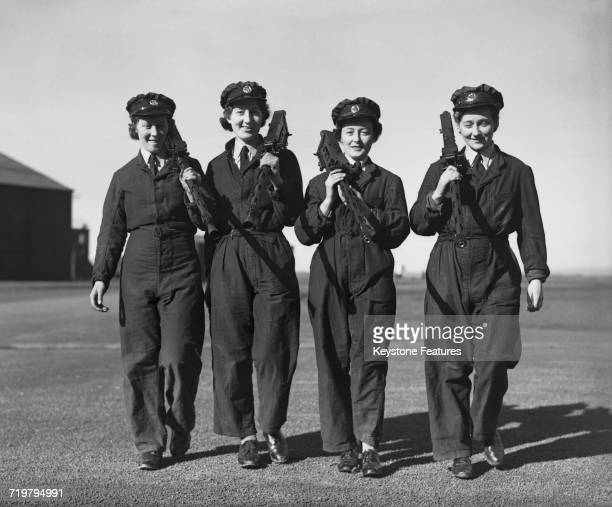 Members of the Women's Auxiliary Air Force carrying aircraft machine guns from an aircraft at No 1 Air Gunners School RAF Pembrey Carmarthenshire...