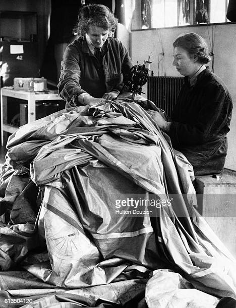 Members of the Women's Auxiliary Air Force repair a deflated weather balloon using an electric sewing machine during World War Two