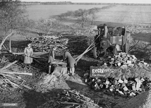 Members of the Women's Land Army at work sawing logs for kindling using a Foden Steam Traction engine on 1st February 1944 at the Royal Sandringham...