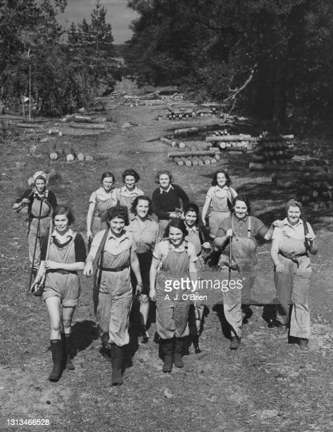 Members of the Women's Land Army march back following a training course in felling and sawing trees and logs on 2nd September 1940 at Bury St....