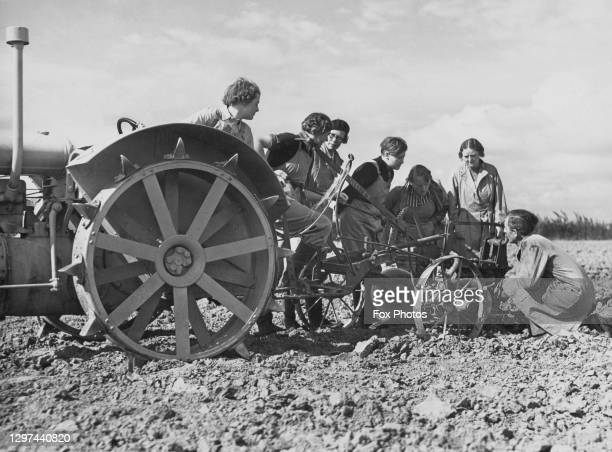Members of the Women's Land Army receive instructions on operating a Standard Fordson tractor and plough attachment on 15th August 1939 at the...