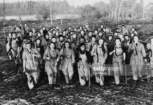Members of the Women's Timber Corps of the Women's Land Army march back following a training course in felling and sawing trees and logs on 8th...