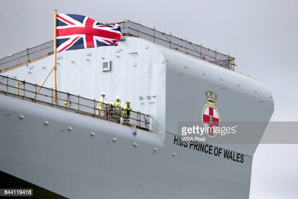 Members of the workforce on the bow of the ship after the naming ceremony of aircraft carrier HMS Prince of Wales at the Royal Dockyard on September...