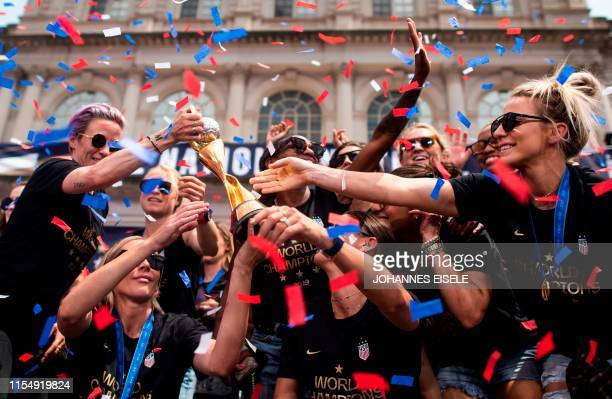 Members of the World Cup-winning US women's team take part in a ticker tape parade with their trophy for the women's World Cup champions on July 10,...