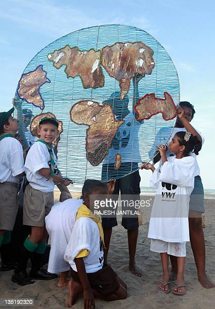 Members of the World Wide Fund for Nature handover a symbolic planet Earth made from wire and beadwork to local children at the Durban Beach on...