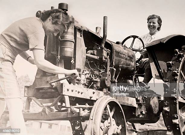 Members of the WVS or Women's Voluntary Service starting a tractor near Watford during World War Two circa 1942