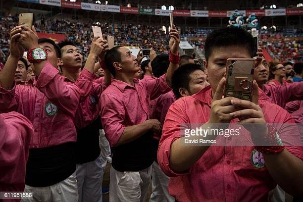Members of the 'Xiquets de Hanghzou' take pictures during the 26th Tarragona Competition on October 1 2016 in Tarragona Spain The 'Xiquets de...