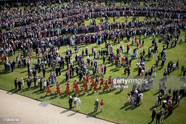 Members of the Yeomen of the Guard march through guests gathered on the lawn during a Garden Party at Buckingham Palace on June 6 2013 in London...