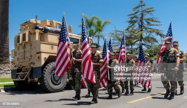Members of the Young Marines march past a USMC MineResistant Ambush Protected vehicle during the Patriotic Parade at the 23rd annual Flag Day...