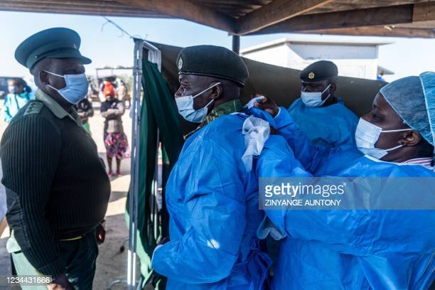 Members of the Zimbabwe National Army don personal protective clothing ahead of a mass community on 3 August 2021, in Cowdray Park township,...