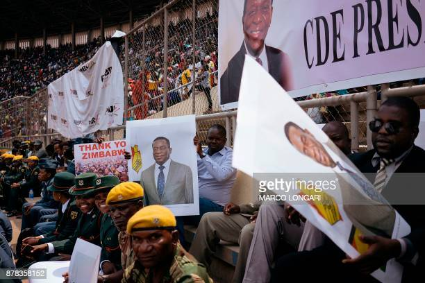 Members of the Zimbabwean military hold posters of newly swornin President Emmerson Mnangagwa at the National Sport Stadium in Harare on November 24...
