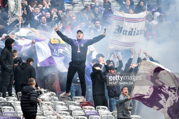 Members of Toulouse's Indians supporters group cheer during the French L1 football match between Toulouse and Guingamp on March 10 at the municipal...