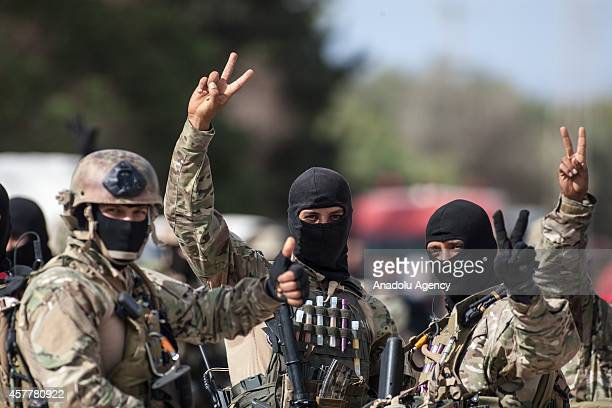 Members of Tunisian Security Forces show victory sign as he stand guard after an operation to a house of suspected terrorists in Manouba Tunisia on...