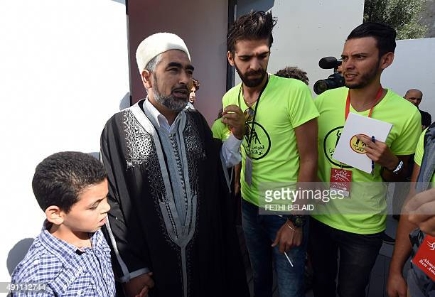Members of Tunisian 'Shams' association for the decriminalisation of homosexuality talk with Tunisian preacher Adel ElAlmi as they prevent him from...