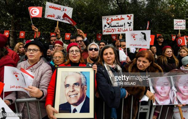 Members of Tunisia's Free Destourian Party shout slogans and hold up protest signs and portraits of late president Habib Bourguiba as they...