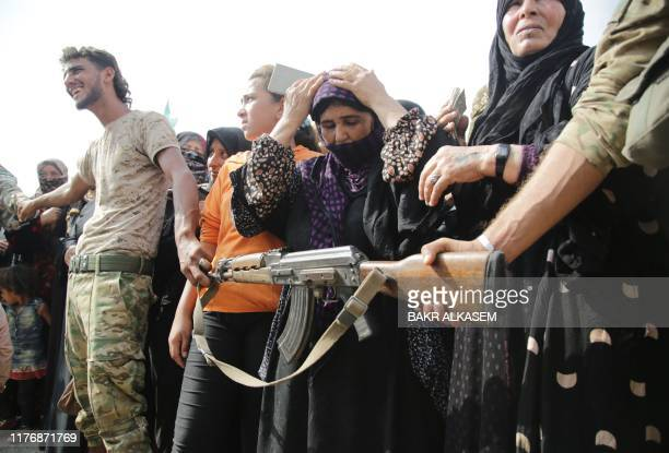 Members of Turkey-backed forces form a cordon to control a crowd of displaced Syrians gathering to receive aid provided by the Turkish Red Crescent...
