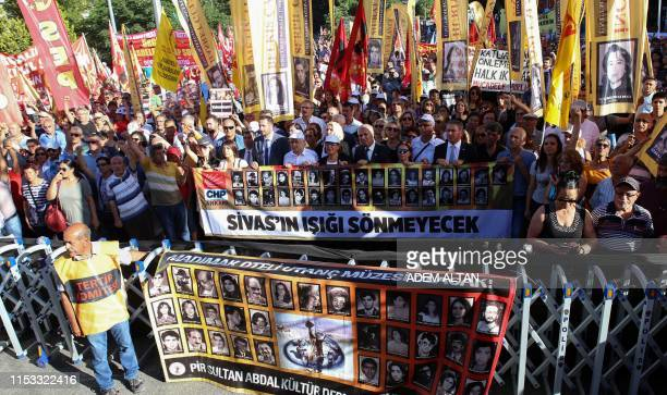 Members of Turkey's Alevi community hold pictures of victims as they march in Ankara on July 2 to mark the 26th anniversary of an arson attack on...