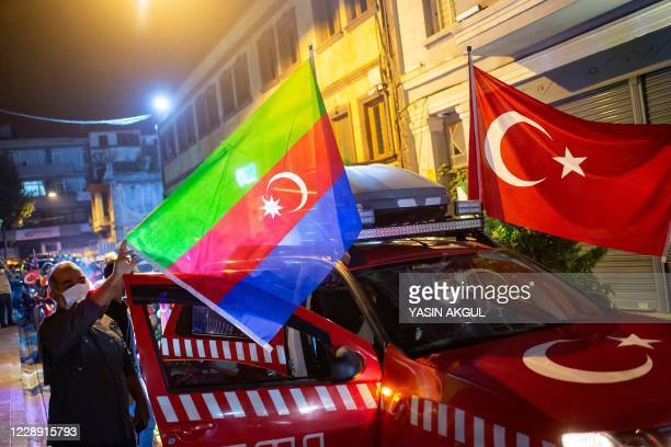 Members of Turkey's Humanitarian Relief Foundation display Turkish and Azerbaijan flags on their vehicle before taking a tour in the city in...