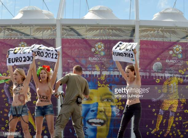 Members of Ukraine's feminist group Femen protest topless as security members try to take them away at the entrance gates of the Olympic stadium in...