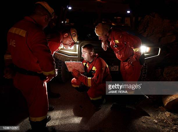 Members of UME read a map in Sant Joan de Labritja on Ibiza island on August 24 2010 All the Mediterranean island's firefighters have been mobilised...
