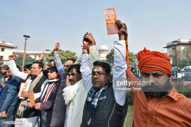 Members of various Hindu groups hold placards during a protest to demand the construction of the Ram Temple, near the Supreme Court on January 10,...