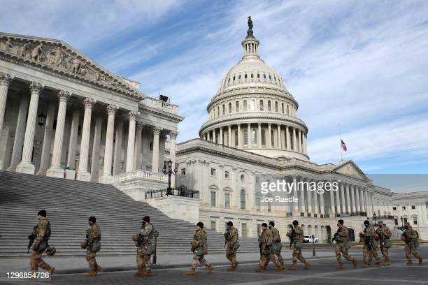 Members of Virginia National Guard walk by the U.S. Capitol on January 17, 2021 in Washington, DC. After last week's riots at the U.S. Capitol...