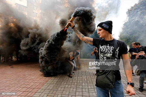 Members of volunteer's battalion Azov and their supporters burn smoke flares near the courthouse in downtown Kyiv, Ukraine, . The Court shall...