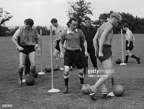 Members of West Ham United Football Club practising dribbling through posts They are taking the advantage of using the grounds of an Essex health...