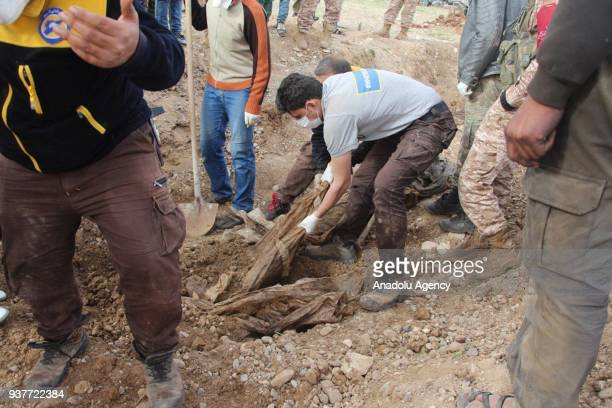 Members of White Helmet take a dead body out of soil after Free Syrian Army fighters found mass grave in recently liberated Kucuk Meydan village...