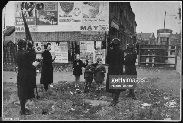Members of William Booth's Christian philanthropic organization assemble on littered wasteground to deliver their tuneful gospel
