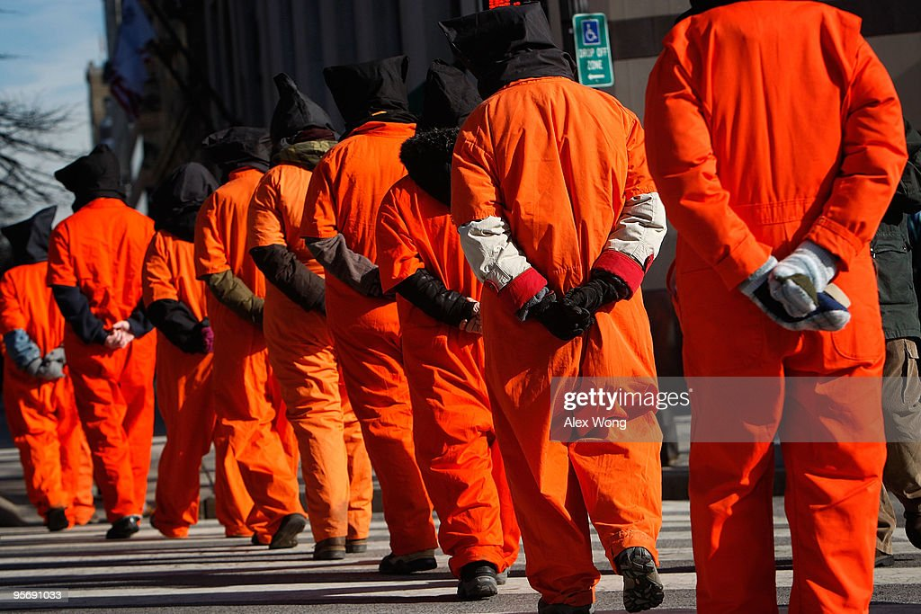 Members of Witness Against Torture wear orange jumpsuits as they march during a protest to mark the eighth anniversary of the opening of Guantanamo Bay detention camp January 11, 2010 in Washington, DC. Protesters called on the Obama Administration to close down the detention facility.