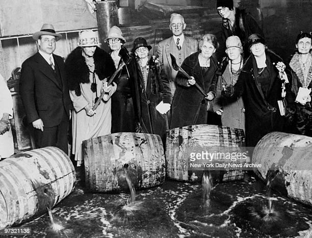 Members of Women's Christian Temperance Union crack open barrels of liquor when 100,000 gallons were seized in raids.